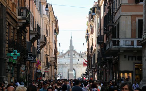 Trecho final da Via del Corso, uma movimentada avenida de comércio. Ao fundo, a Piaza del Popolo com seu Obelisco.