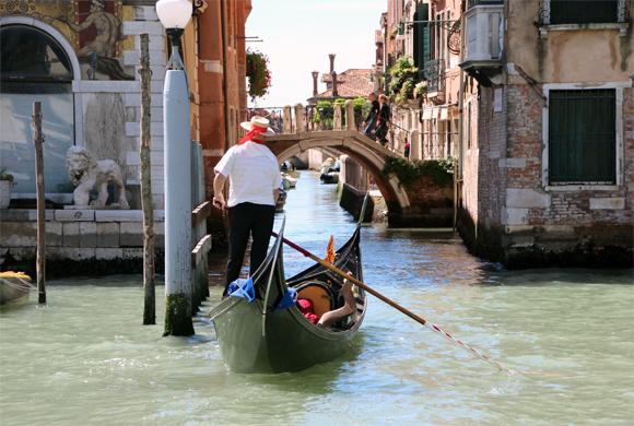 Um gondoleiro manobra sua gôndola para entrar em um canal. Vale usar seu remo ou usar o pé para impedir de bater nas paredes das casas...