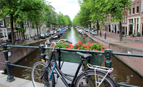 Um lindo canal em Amsterdam, com direito a flores e bicicleta encostada na ponte...