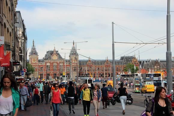 A movimentada Amsterdam, na imagem a Damrak e nos fundos a Estação de Trens Amsterdam Centraal.
