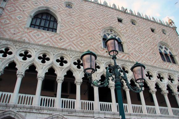 Detalhe para a fachada externa, as delicadas colunas, o mosaico branco-e-rosa e os postes mais que românticos de Veneza.